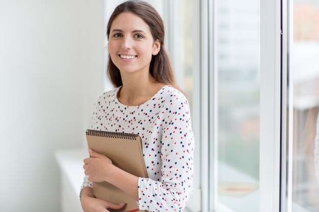 Menina sorrindo com o bloco de notas