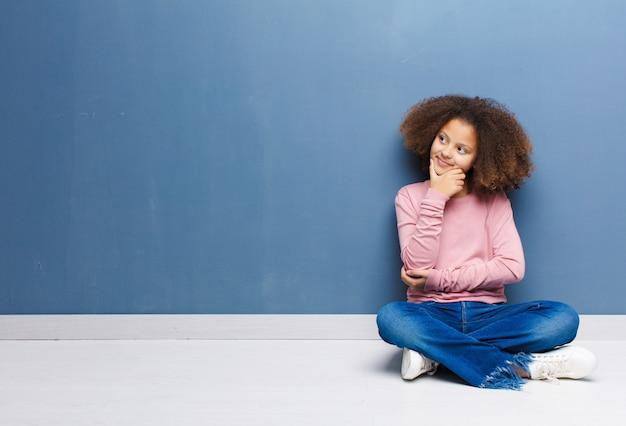 Menina sorrindo com uma expressão feliz e confiante com a mão no queixo, pensando e olhando para o lado sentado no chão