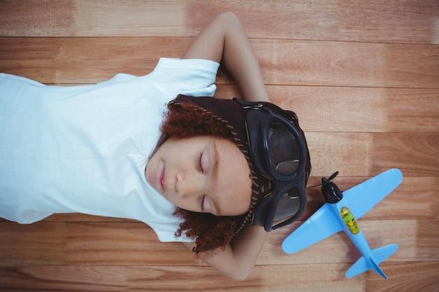 Menina sorrindo dormindo no chão usando óculos e chapéu de aviador