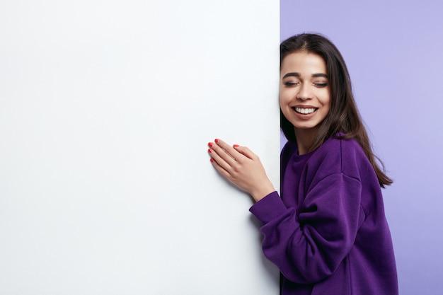 Menina sorrindo e abraçando um banner vertical em branco com os olhos fechados