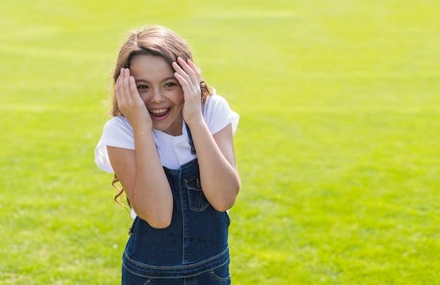 Menina sorrindo e brincando lá fora