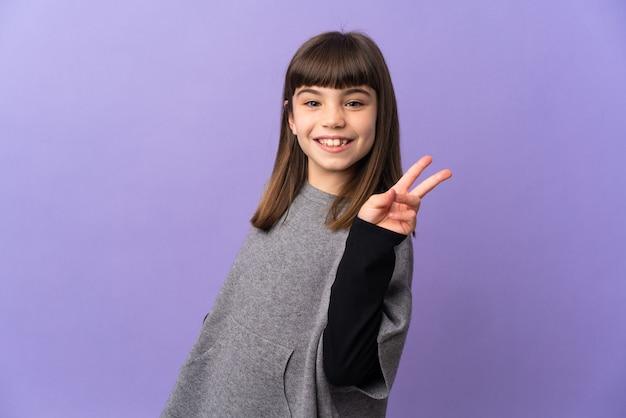 Menina sorrindo e mostrando o sinal da vitória sobre uma parede isolada
