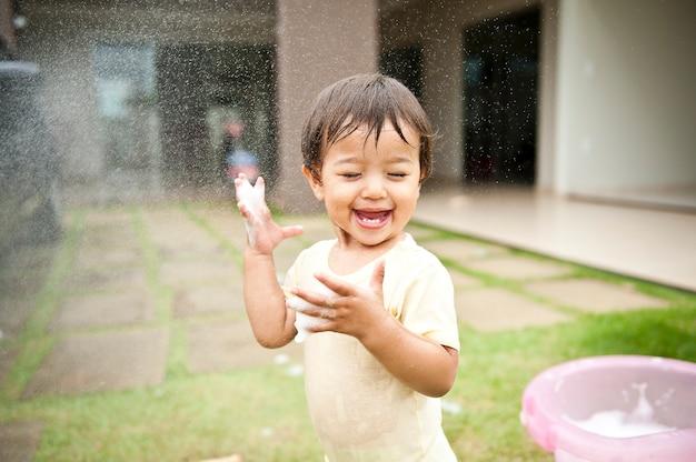 Menina sorrindo e se divertindo com a água