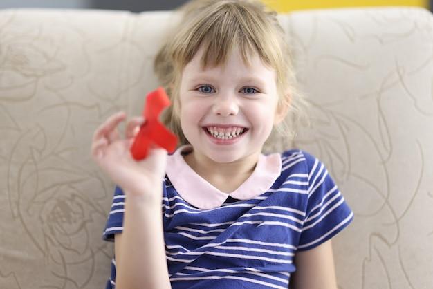 Menina sorrindo e segurando um retrato de fita vermelha na mão