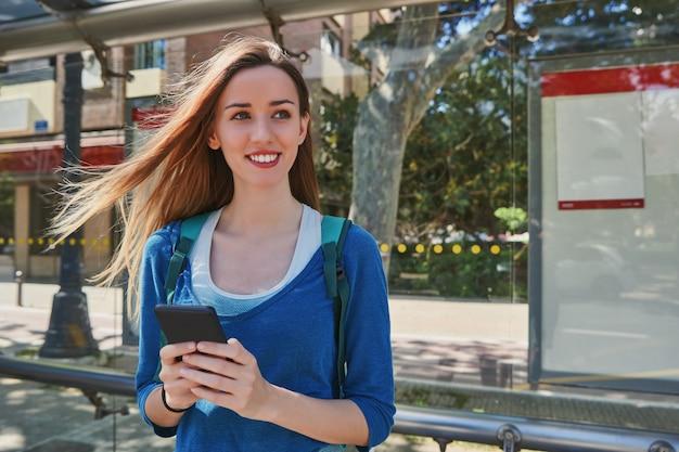 Menina sorrindo e usando o celular enquanto espera no ponto de ônibus