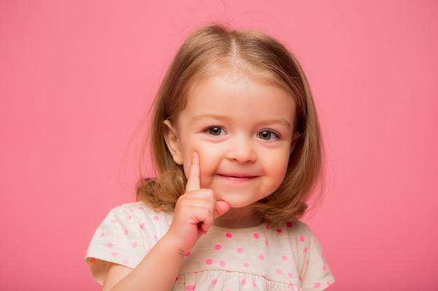 Menina sorrindo em fundo rosa