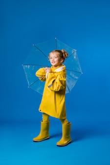 Menina sorrindo em uma capa de chuva amarela e botas de borracha, segurando um guarda-chuva