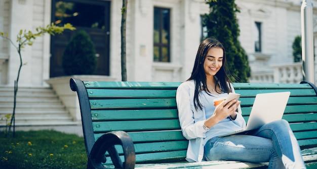 Menina sorrindo enquanto bebe um café no banco