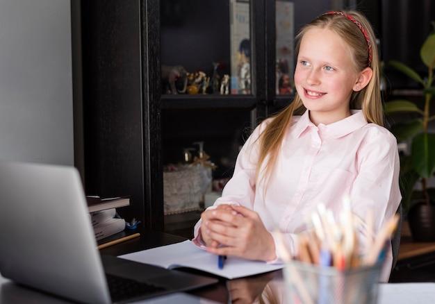 Menina sorrindo enquanto fazia uma aula on-line
