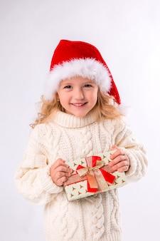 Menina sorrindo no chapéu de papai noel segurando a caixa de presente em fundo branco