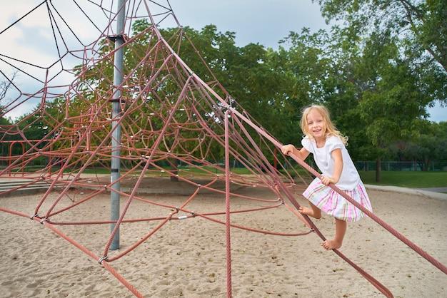 Menina sorrindo, olhando, criança brincando na rede de escalada. ao ar livre em dia ensolarado de verão.
