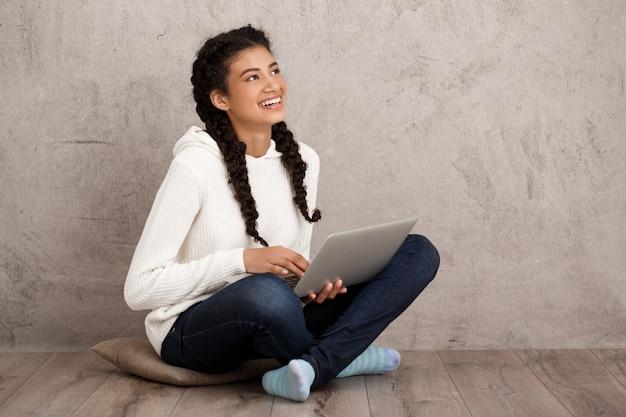 Menina sorrindo, segurando laptop, sentada no chão parede bege