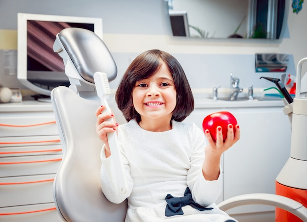 Menina sorrindo, segurando nas mãos uma escova de dentes e uma maçã.