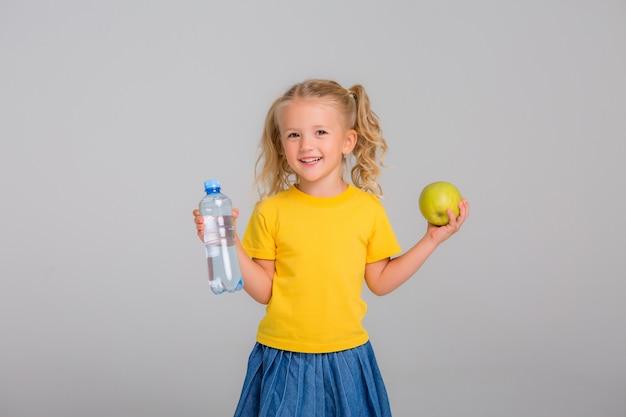 Menina sorrindo segurando uma maçã e uma garrafa de água