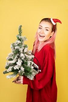 Menina sorriu com árvore de ano novo