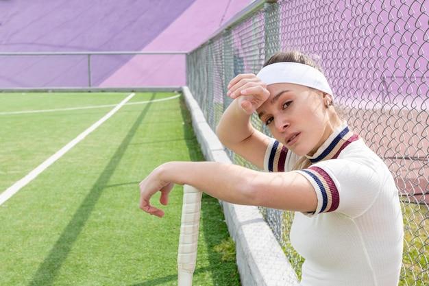 Menina suando em um campo de tênis