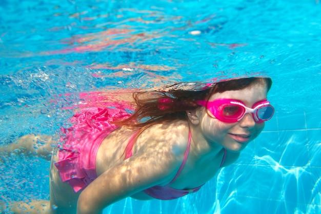 Menina subaquática rosa biquíni azul piscina