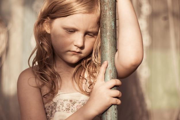 Menina suja triste ao ar livre