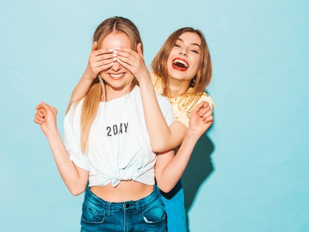 Menina surpreendendo sua melhor amiga feminina. modelo cobrindo os olhos e abraçando por trás.