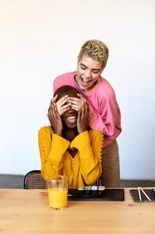 Menina surpreendendo sua melhor amiga. modelo cobrindo os olhos e abraçando por trás. duas garotas surpresas. mulheres se divertindo e mostrando emoções faciais