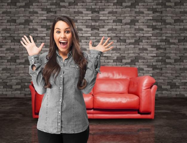 Menina surpreendida com um sofá fundo vermelho