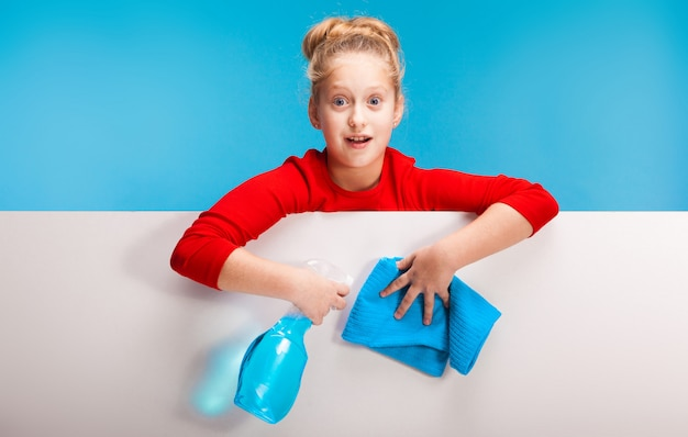 Menina surpreendida com um spray e um pano azul