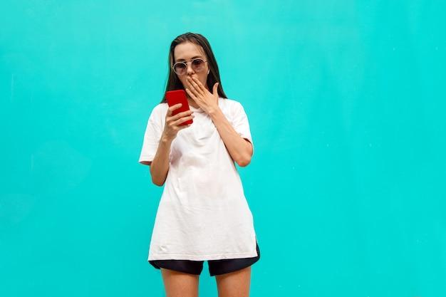 Menina surpreendida ocasional que olha o smartphone