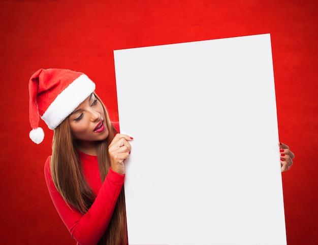 Menina surpreendida olhando para um cartaz em branco