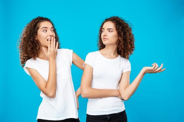 Menina surpreendida olhando sua irmã gêmea sobre parede azul