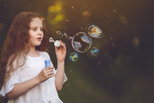 Menina surpreendida que funde para fora uma bolha de sabão na forma de um cão ou gato. magia, desejo, conceito de ano novo.
