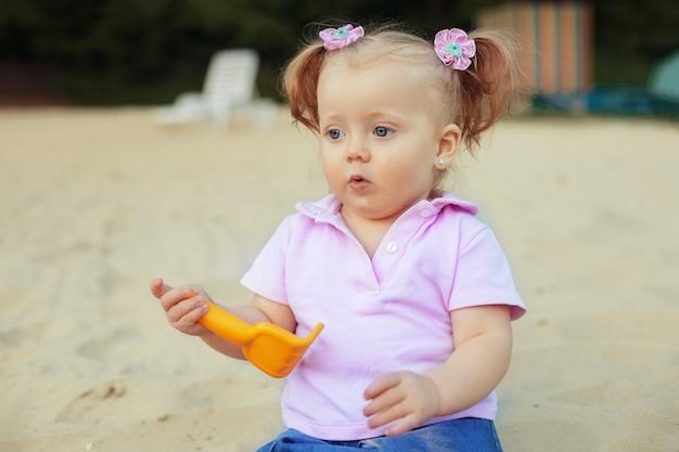 Menina surpreendida que joga na areia.