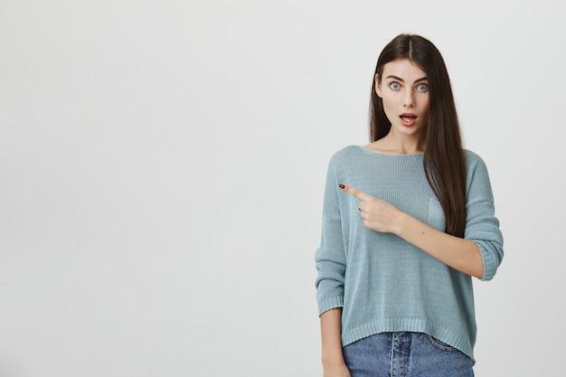 Menina surpreendida soltar a mandíbula e apontando à esquerda surpreso