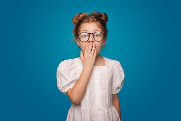 Menina surpresa cobrindo a boca, posando com um vestido na parede azul do estúdio