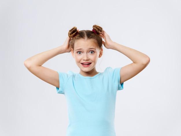 Menina surpresa com as mãos na cabeça