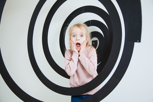 Menina surpresa com rosto emocional em espiral preta no estúdio.