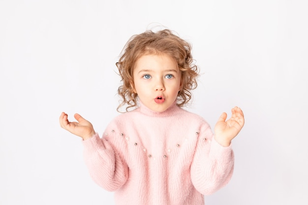 Menina surpresa com roupas de inverno rosa em fundo branco, espaço para texto