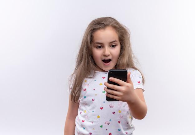 Menina surpresa da escola vestindo camiseta branca olhando no telefone em fundo branco isolado