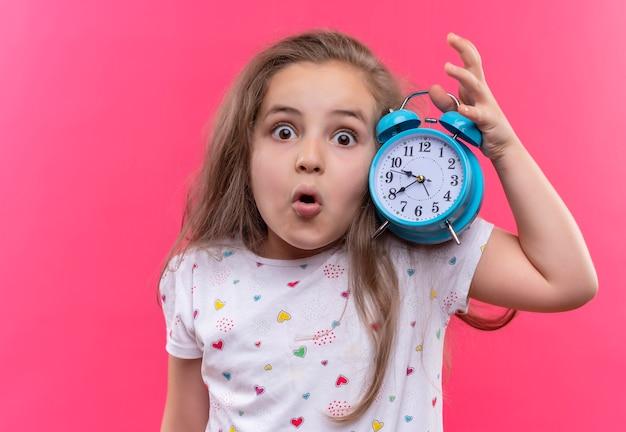 Menina surpresa da escola vestindo camiseta branca segurando o despertador no fundo rosa isolado