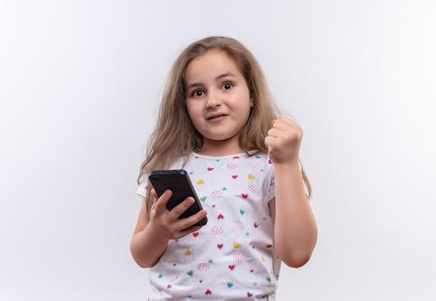 Menina surpresa da escola vestindo camiseta branca, segurando o telefone e levantando o punho em um fundo branco isolado