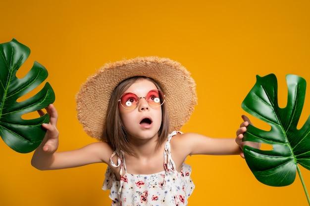 Menina surpresa de óculos e um chapéu de palha em um fundo amarelo no estúdio