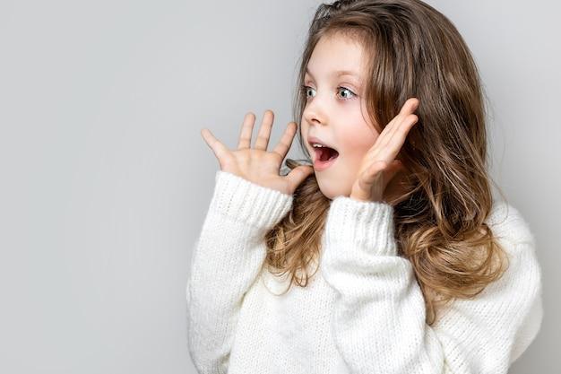 Menina surpresa desvia o olhar e segura o rosto com as mãos em um fundo claro