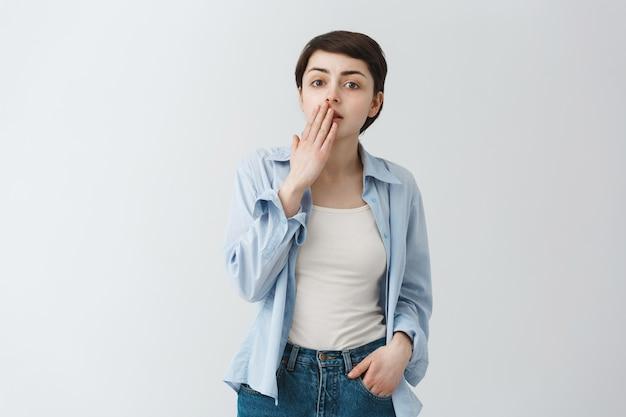 Menina surpresa ofegando e cobrindo a boca maravilhada