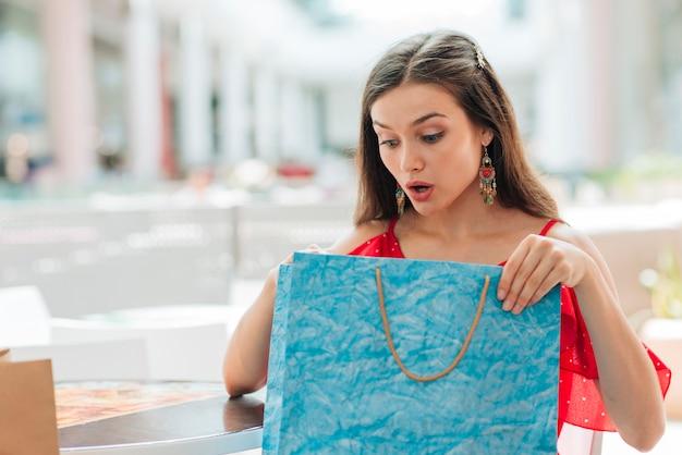 Menina surpresa, verificando suas roupas novas