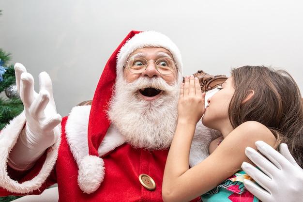 Menina sussurrando no ouvido do papai noel