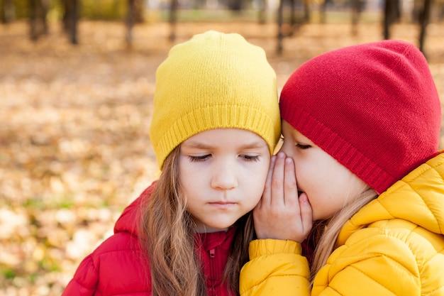 Menina sussurrando para a irmã. crianças, duas amigas fofas pequenas brincam no outono
