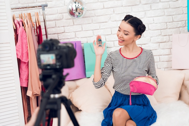 Menina sustenta brinco colorido para a câmera.