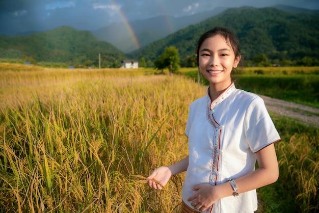 Menina tailandesa a pé na fazenda de arroz e arroz em lamduan café de pano