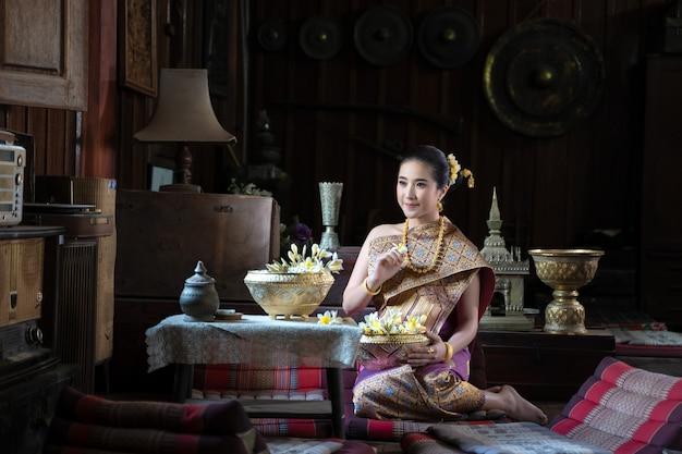 Menina tailandesa bonita no traje tradicional do vestido que senta-se na casa de madeira antiga, mulher tailandesa no traje tradicional de tailândia.