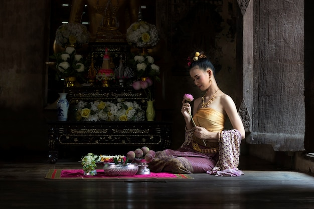 Menina tailandesa das mulheres bonitas no traje tailandês tradicional com ayutthaya do templo.