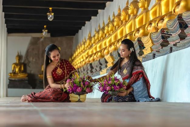 Menina tailandesa das mulheres bonitas que guarda lótus da mão no traje tailandês tradicional com ayutthaya do templo, cultura da identidade de tailândia.